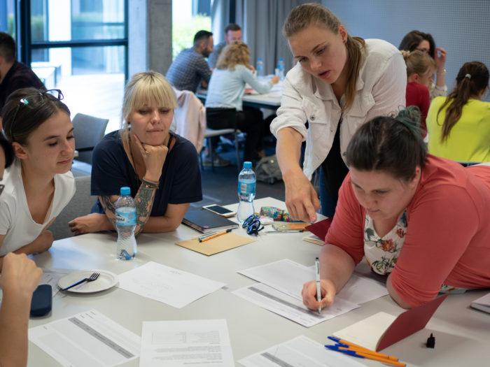 Fotografia osób pracujących razem na zadaniem grupowym na warsztatach UX w praktyce