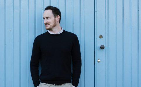 Rhys Nealon na tle niebieskich drzwi.