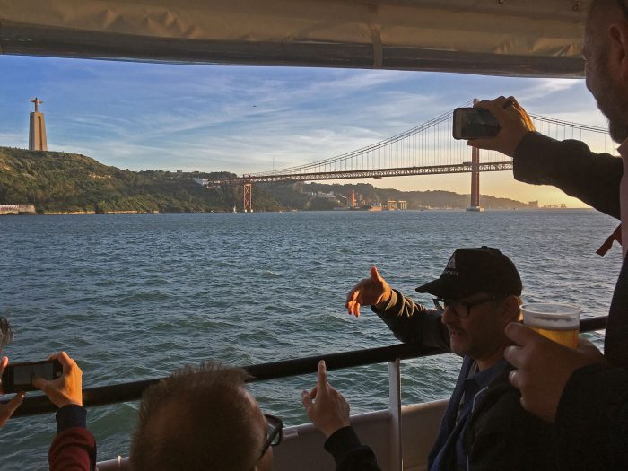 Trzy osoby fotografujące zachód słońca nad Lizboną — z łódki płynącej po rzece Tag. W tle pomnik Jezusa.